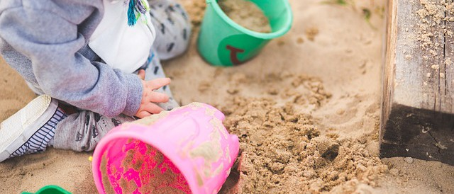 child playing in sand with pink and yellow buckets
