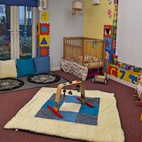 A baby room with a cot in the corner, colourful displays and a padded mat with play equipment
