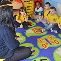 Small children sitting on a mat in a circle listening to a nursery assistant