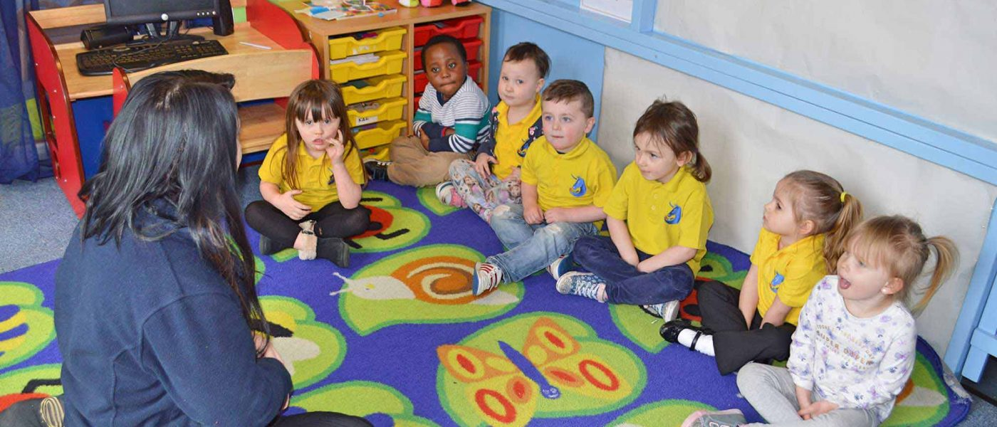 Children sitting on a colourful mat in a circle listening to nursery assistant telling a story.