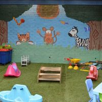 A covered outdoors area with grass, play equipment such as rockers and a colourful, painted mural on a brick wall