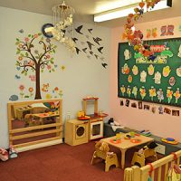 A room corner with play equipment, wall displays and a mural of a tree and birds