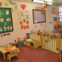 A large room with a gate divider with toys and colourful wall displays
