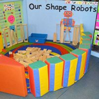 Lots of wooden building blocks inside a colourful, contained area and a robot display on the wall