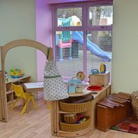 a corner of a room, entered by an arch, with a table and a chair and toys with a view of play equipment i n the garden