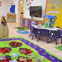 A large room with a colourful mat, play equipment and a table and chairs