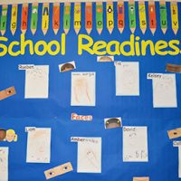 A wall display titled 'School Readiness' with numbers and writing from children