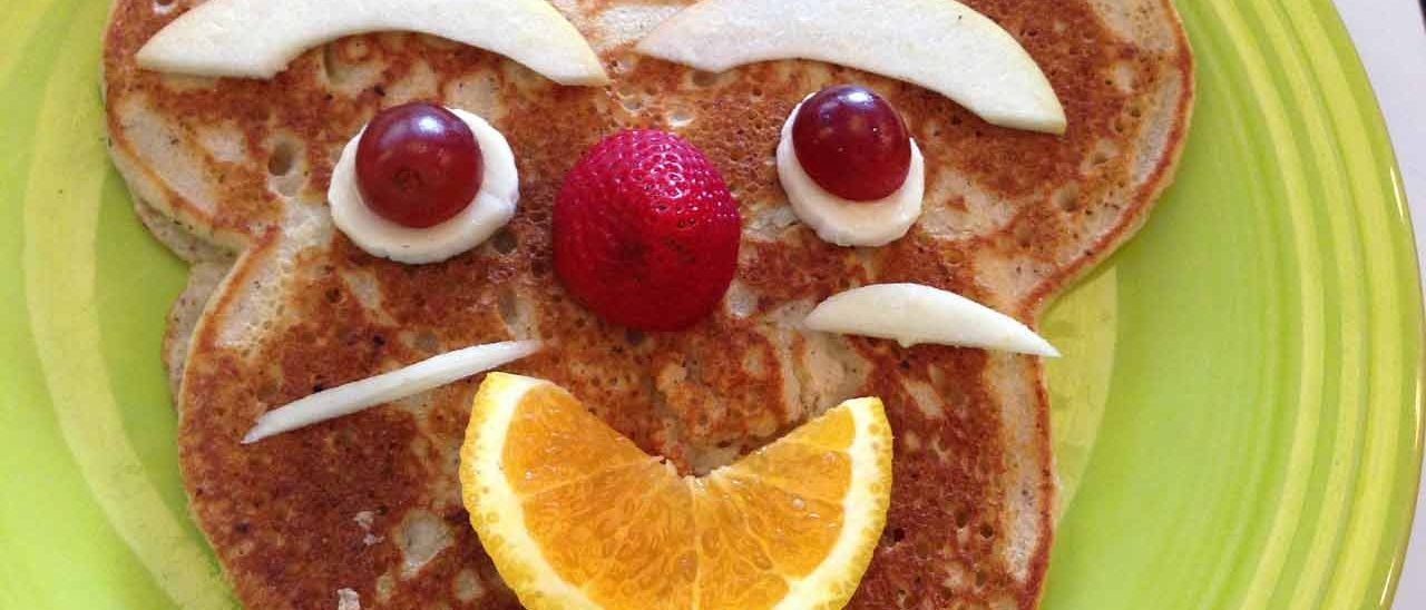 A child's plate with pancakes and fruit arranged in the shape of a bear's face