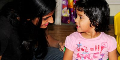 A teacher smiling at a young child